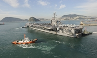 Tugboats pulling the USS George Washington out of the port of Busan, South Korea, October 2011.