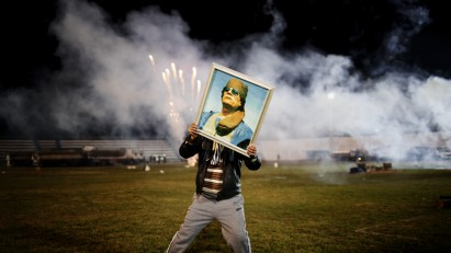 Libya, March 2011. A Qaddafi supporter holds a portrait of the Libyan leader as fireworks go up in the background on a soccer field in a suburb of Zawiyah where government minders took a group of foreign journalists to attend a staged celebration. Photo by Moises Saman/MAGNUM