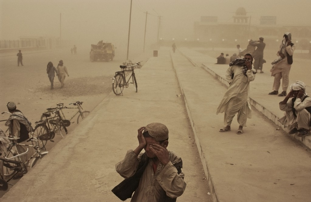 Afghanistan, March 2005. A boy covers his eyes during a sandstorm in the southern city of Kandahar.  Photo by Moises Saman/MAGNUM