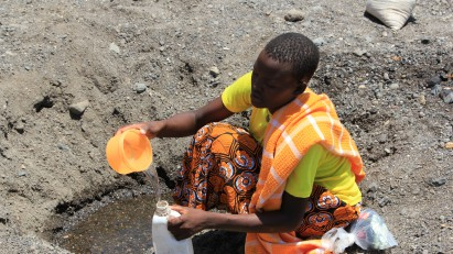 28 Hero image A woman scoops water in a dry riverbed near Kataboi village in remote Turkana in northern Kenya - credit DFID