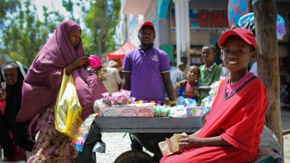 SOMALIA, Mogadishu: In a photograph taken and released by the African Union-United Nations Information Support Team 05 August 2013, a woman shops at a roadside stall in Hamar Weyne market in the Somali capital Mogadishu. 06 August marks 2 years since the Al Qaeda-affiliated extremist group Al Shabaab withdrew from Mogadishu following sustained operations by forces of the Somali National Army (SNA) backed by troops of the African Union Mission in Somalia (AMISOM) to retake the city. Since the group's departure the country's captial has re-established itself and a sense of normality has returned. Buildings and infrastructure devastated and destroyed by two decades of conflict have been repaired; thousands of Diaspora Somalis have returned home to invest and help rebuild their nation; foreign embassies and diplomatic missions have reopened and for the first time in many years, Somalia has an internationally recognised government.. AU-UN IST PHOTO / STUART PRICE.