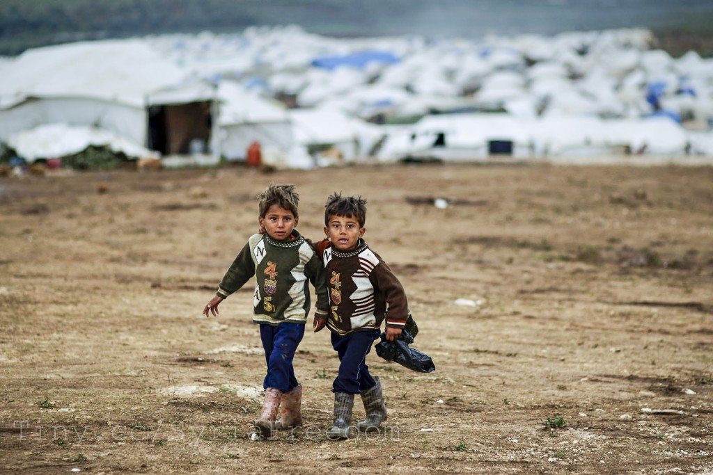 Syrian boys, whose family fled their home in Idlib, walk to their tent, at a camp for displaced Syrians, in the village of Atmeh, Syria. Credit FreedomHouse.
