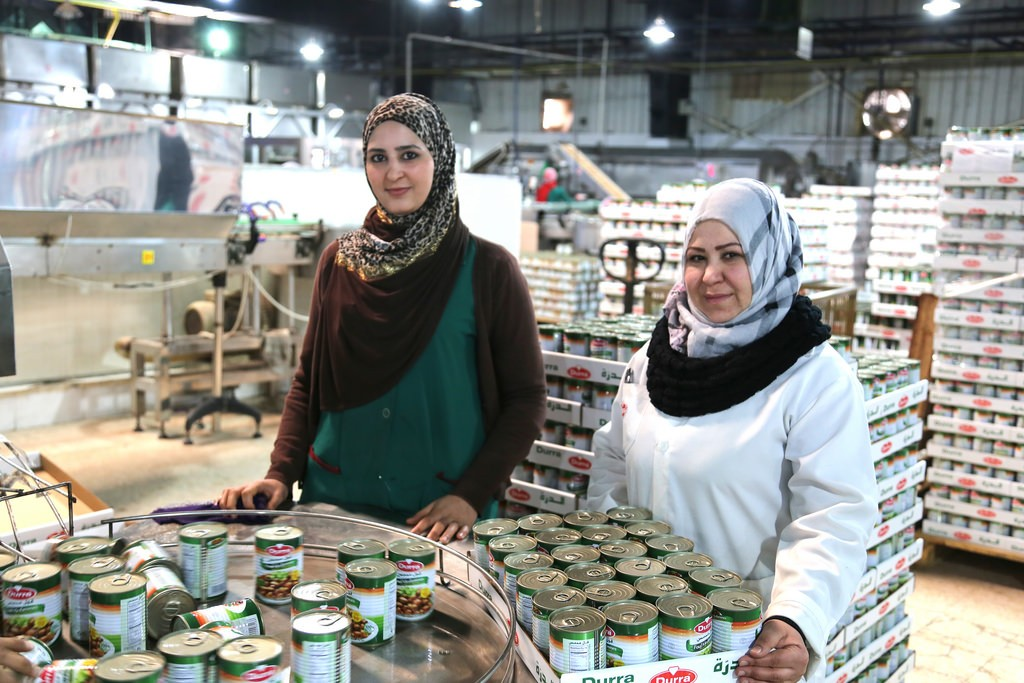 Anood from Jordan and Salma from Syria, working together in a Syrian-owned food processing factory Jordan.