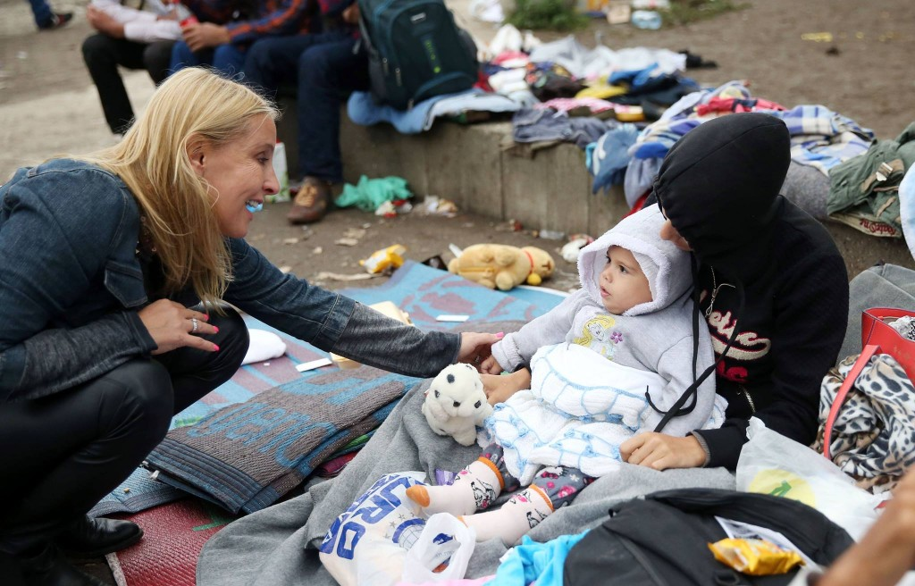 Ana Divac talking to refugees in Mikaliste park in Belgrade.