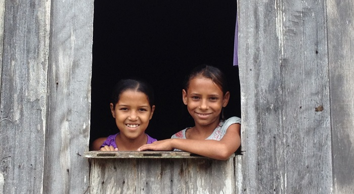 Sisters aged 8 and 9 take care of their brother, who is under 5, while their mother works.