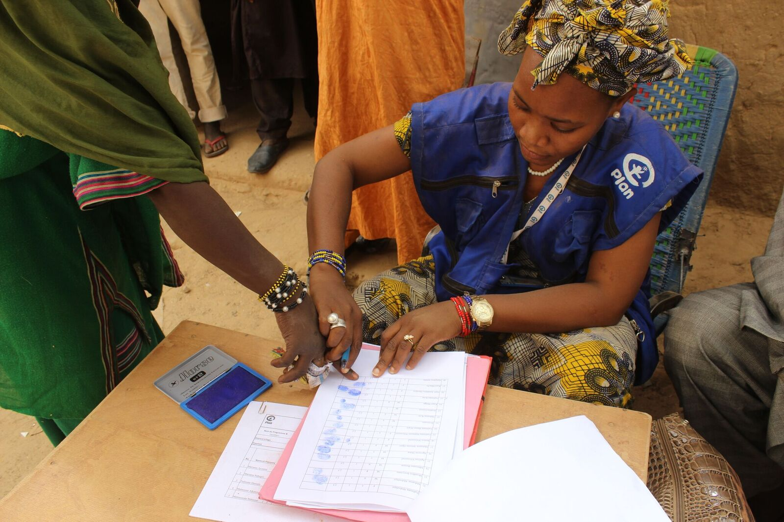 Plan International, Mali. Fingerprinting the list before receiving food assistance
