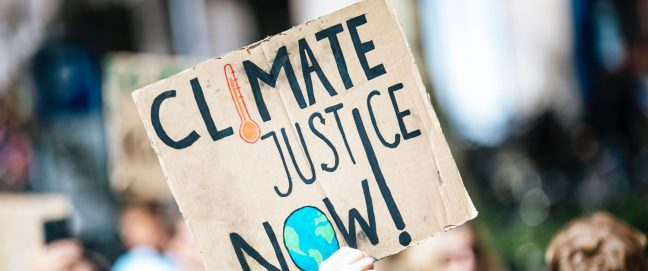 An activist holds up a sign that reads 'Climate Justice Now'.